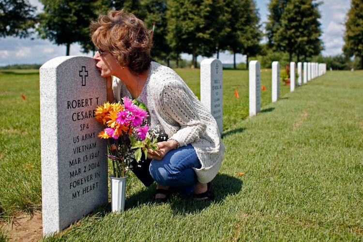 Francesca Cesare kisses her late husband's tombstone  on Thursday, August 14, 2014 in Saratoga National Cemetery in Saratoga, N.Y.  Robert died in 2014 of three different types of cancer related to exposure to Agent Orange while serving in the United States Army during the Vietnam War.