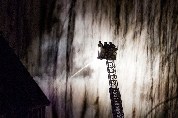 Firefighters of the Ramsey fire department project water onto the Avalon apartment complex during a 5-alarm fire on Tuesday, Jan. 21, 2015 in Edgewater, N.J.  The fire, which displaced some 1,000 people was caused by a plumbing repair that ignited a fire in the wall which then spread through the building.  No fatalities were reported.