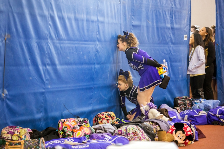 Hamburg Varsity competitive cheer teammates Maya Fagnan, below, and Ava O'Hara, above look through curtain holes at another team's performance during the  NYSPHAA State Cheerleading qualifiers cheer competition on March 7, 2015 in Henrietta, N.Y.