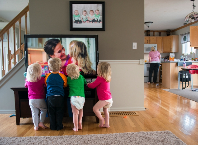 The Larson quadruplets (Left to Right) Ashlyn, Brody, Cooper, and Kylie watch television as Courtney prepares a snack for them in the kitchen. Courtney often turns on the television to distract the children while she prepares food or does chores around the house. Nov. 16, 2014.