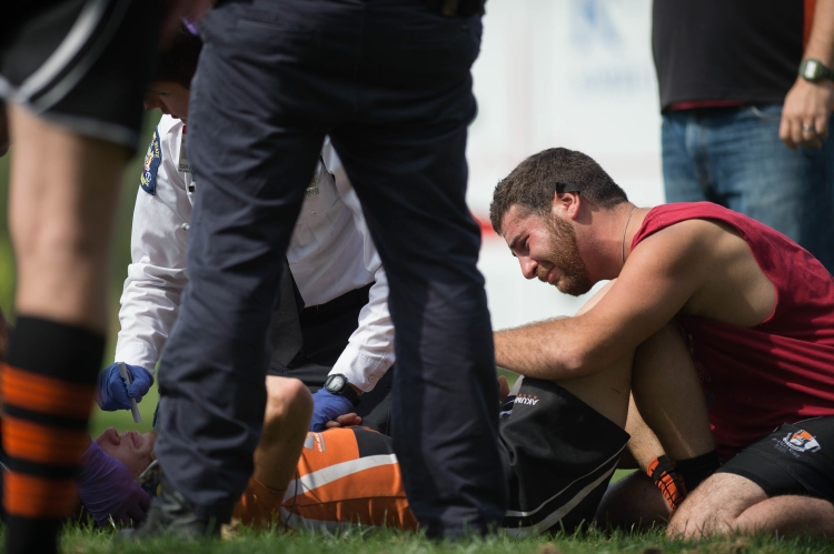 Close friend Anthony Adams, right, looks on as Thomas L. McNulty, RIT ambulance, checks the vitals of Christian Feickert after a brutal hit on the Rugby Field on the Rochester Institute of Technology campus in West Henrietta, N.Y. on Sept. 26, 2015. Christian later found out at the hospital that he had a severe concussion.