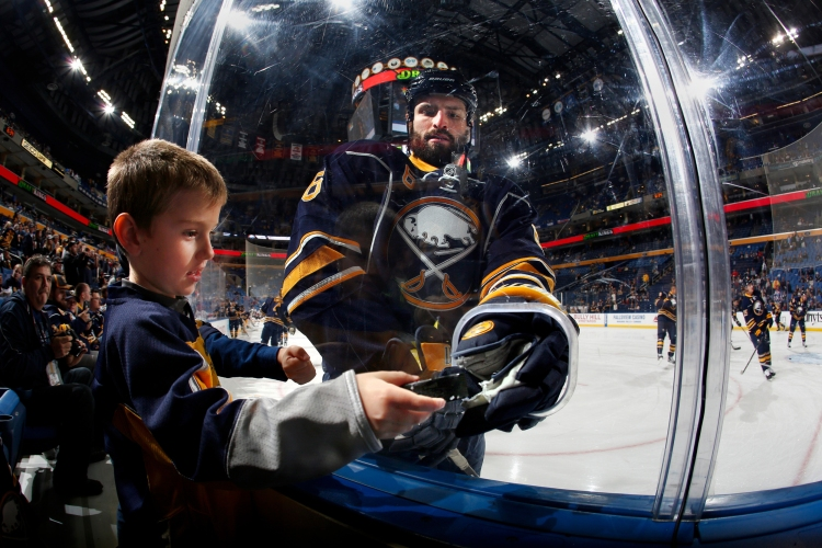 Cody McCormick (8) of the Buffalo Sabres hands a puck to Lawson Zlotek (cq) during warmups before a game against the Ottawa Senators at the First Niagara Center on Oct. 8, 2015 in Buffalo, New York.