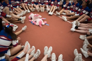 The Fairport High School Cheerleading team sits in a circle around their lucky stuffed unicorns waiting for the results of the Section V Cheerleading Fall Sectionals held at Rochester Institute of Technology's Gordon Field House Oct. 31, 2015 in Henrietta, N.Y. The team has had their lucky unicorns for around 10 years, and they refuse to wash them. The Fairport High School cheerleading team won first place in the Division I Large category.