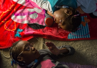 Mary, left, lays on the floor next to her sister, Keira, right, while watching a movie in the family room on October 19, 2014 in East Rochester, N.Y.