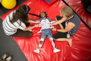 Keira Roko, center, lays on a mat as Chaney, left, and Physical Therapist Karen Tarp put on her back brace inside C.T. Aquatics on August 31, 2015 in Rochester, N.Y.