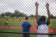 Shawn Abraham hangs onto the fence while waiting to bat during a game of beep baseball at Camp Abilities, hosted at the Maryland School for the Blind on June 30, 2015 at Baltimore, Md.