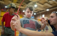 Chris Parrish Jr.,left, of the Clarksville Scouts troop 737 looks downrange as Taylor Runion, 10, center, is taught by camp instructor Matt Mescall, right, how to use a bow and arrow during an archery shooting activity at Camp Abilities, hosted by the Maryland School for the Blind on June 30, 2015 Baltimore, Md.