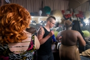 """Summary: Newlyweds, Tyler and Jessica Rinallo, experience many of the same challenges other couples face as they adjust to married life together. In addition to the simple changes, their lives are transforming in more complex ways as Tyler transitions from being a female to a male. Tyler Rinallo in the Tilt Nightclub dressing room with two drag queens before his performance on April 9, 2015. Most of the drag kings and queens perform twice a night interacting with the crowd while lip-syncing and dancing to music, """"When I first started performing I was a very shy person and by performing on stage it has allowed me to break out of my shell,"""" said Tyler."""