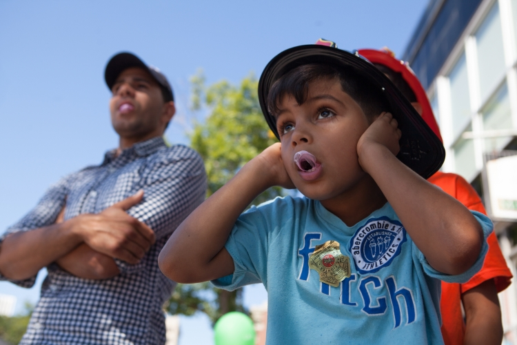 Jahdiel Marrero, 8, of Rochester, covers his ears as fire trucks blare their horns during the annual Rochester Labor Day parade along East Avenue in Rochester, N.Y., on Sept. 5, 2016. The parade featured union workers, public officials, and local first responders, among others.