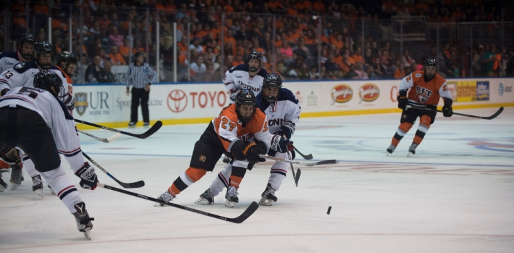 Alex Perron-Fontaine (#27) of the Rochester Institute of Technology Tigers fights for a puck against a member of the University of Connecticut Huskies hockey team, at Blue Cross Arena, on Oct. 15, 2016, in Rochester, N.Y. The game ended in an overtime tie, 1-1.