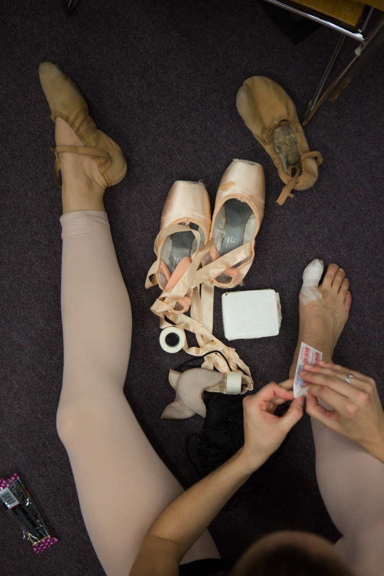 Amy Stuart, 23, tapes her feet in order to switch from ballet flats to pointe shoes for the Rochester City Ballet (RCB) rehearsal of The Nutcracker, in Rochester, N.Y., on Oct. 26, 2016. Stuart has been dancing since she was 3-years-old and has been with the RCB for two seasons, where she began her professional ballet career.