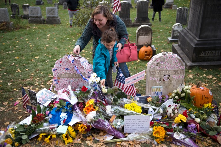 Voters place their stickers on Susan B. Anthony's grave in Mount Hope Cemetery after being able to vote for a woman on a major party ballot for the first time in Rochester, N.Y. on Nov. 8, 2016.