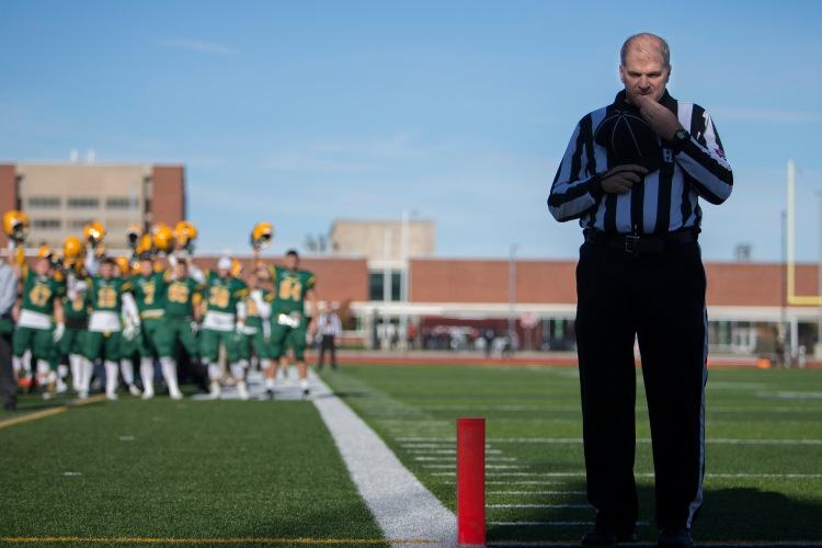 Referee Steve Campbell stands in the end zone for the National Anthem at the Bob Boozer Field on the college of Brockport campus in Brockport, N.Y. on Nov. 12, 2016.