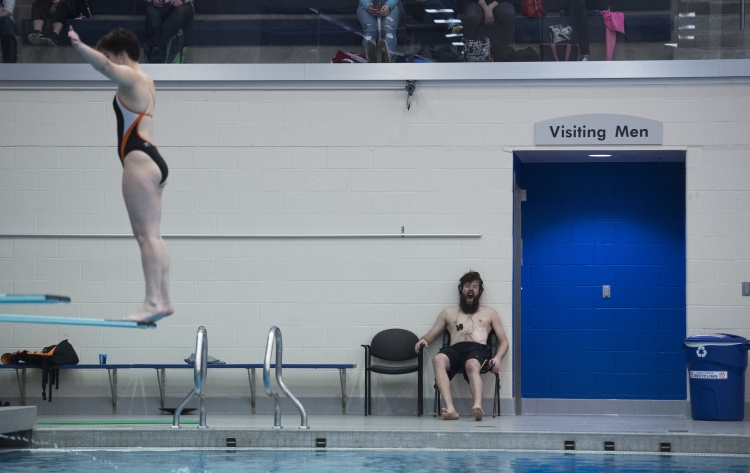 Patrick McFadden, a freshman from Alfred State University, yawns while Madeline Wolters, a Sophomore from Rochester Institute of Technology (RIT), performs a one meter dive at Judson Pool on the RIT Campus, on Nov. 19, 2016, in Henrietta, N.Y. RIT won the meet, with a women's score of 148-96, and a men's score of 186.5-103.