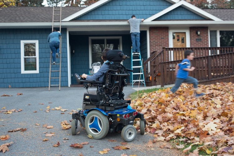Josh Nodine, 8, watches as his parents setup christmas lights and Caleb Nodine, 6, runs into a leaf pile on Friday, November 18, 2016. Josh was diagnosed with Cerebral Palsy as an infant.