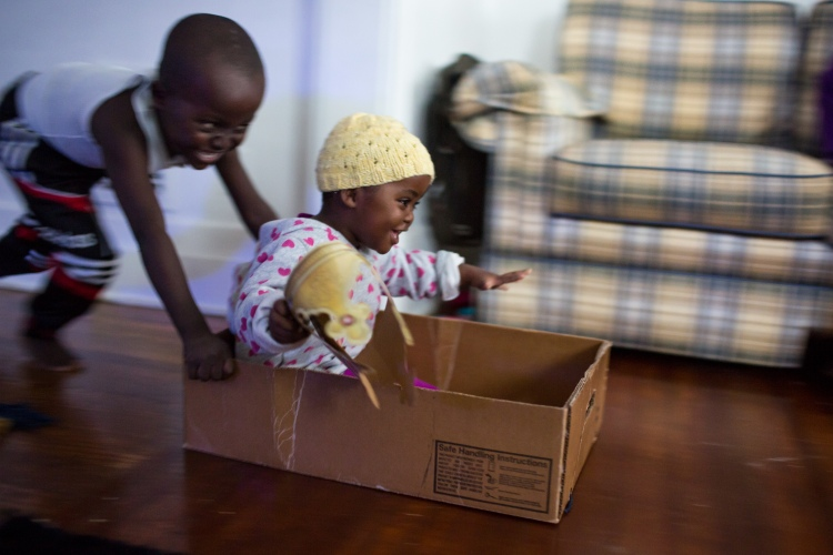 Hassan Abdikadir, 5, pushes his sister, Khadijo, 2, across the living room floor in a cardboard box, as she holds a paper crown from their first ever visit to a Burger King earlier in the day, on Dec. 9, 2016, in the family's newly settled apartment in Rochester, N.Y. The Abdikadir family moved to Rochester in November of 2016 from a refugee camp in Kenya, after leaving their native home of Somalia nearly ten years prior.
