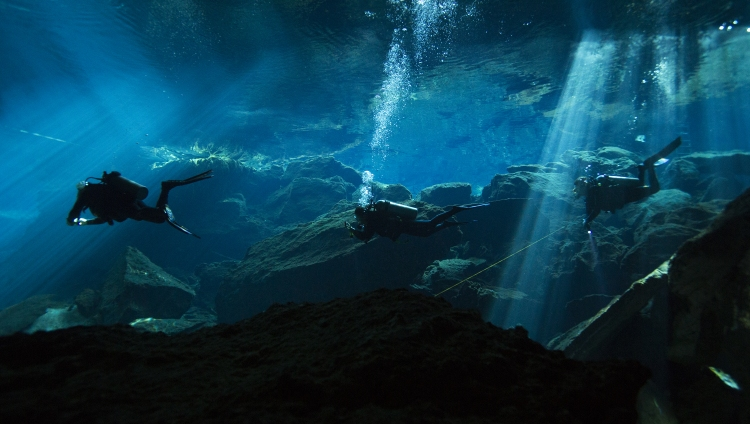 Three divers enter Hermano Pequeno cenote at Chauc Mool, on Jan. 11, 2017, in Quintana Roo, MX.  Cenotes are sinkholes made from collapsed limestone and filled with water, which contain caverns and well as caves.