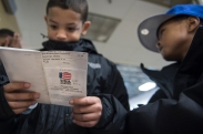 Jay'Von Cummings, 10, (left) looks over the USA Boxing rules and regulations passbook given to him at the West Area Athletic Education Center in Syracuse, N.Y. on Dec. 10, 2016. Jay'Von's passbook was initially stolen and lost when their family car got broken into a couple weeks prior to the tournament starting.